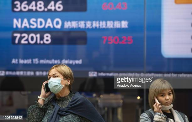 A women wearing a face mask as a precautionary measure against the coronavirus oficially named COVID19 is seen in front of a stock market display...