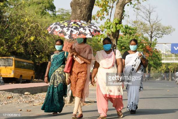 Women wearing a face mask seen using an umbrella on a hot summer day, on May 13, 2020 in Patna, India.