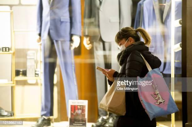 Women wearing a face mask walks by closed shops on Regent street on March 19, 2020 in London, England.