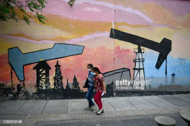 Women wearing a face masks walk past a mural depicting an oil pump in a street of Caracas, on April 14, 2021. - Amid crisis, hiperinflation, fall of...