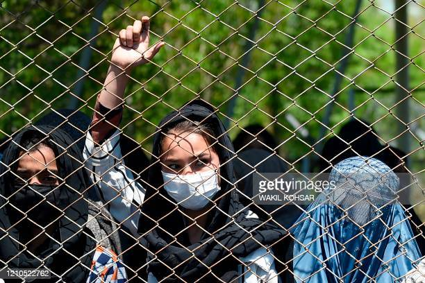 Women wearing a facemask peeks from a iron fence as they wait to receive free wheat from the government emergency committee during a...