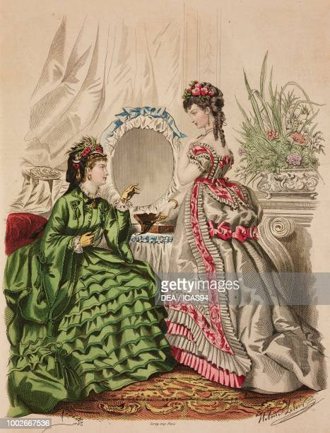 Women wearing a green walking dress and white evening dress with pink inserts Madame BreantCastel designs France coloured engraving from La Mode...