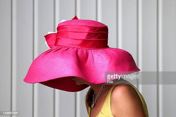 A women wearing a hat walks through the paddock during the 138th running of the Kentucky Derby at Churchill Downs on May 5 2012 in Louisville Kentucky