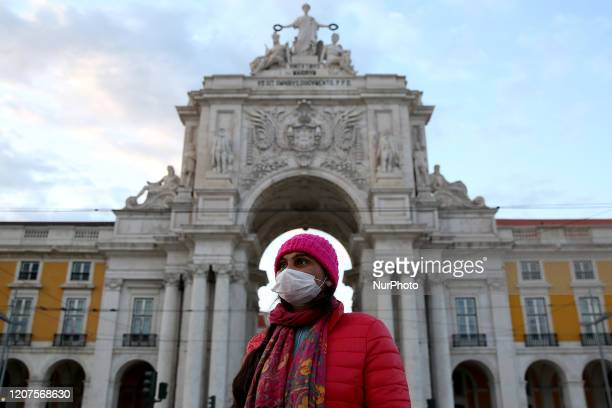A women wearing a mask walks at the Terreiro do Paco square in downtown Lisbon Portugal on March 17 2020 With 448 cases of infection already...