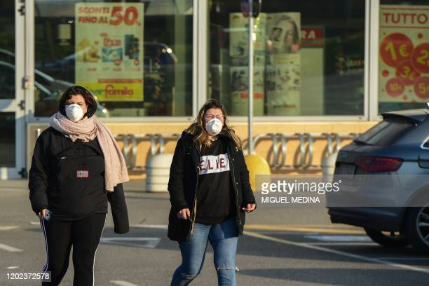Women wearing a protective respiratory mask leave after finding out the local supermarket's closed in Codogno, southeast of Milan, on February 22,...