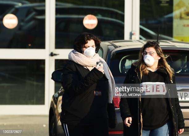 Women wearing a protective respiratory mask leave after finding out the local supermarket's closed in Codogno southeast of Milan on February 22 2020...