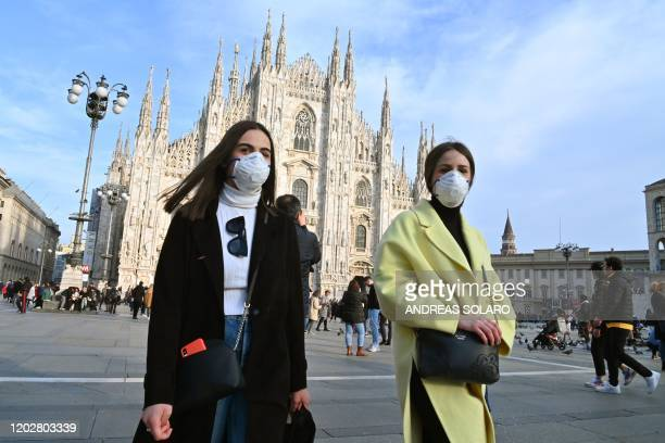 TOPSHOT Women wearing a respiratory mask walk across Piazza del Duomo in central Milan on February 23 2020 Tens of thousands of Italians prepared for...