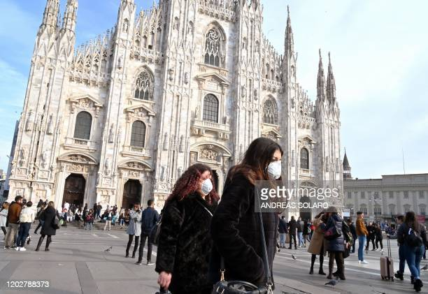Women wearing a respiratory mask walks across Piazza del Duomo in central Milan on February 23 2020 Tens of thousands of Italians prepared for a...