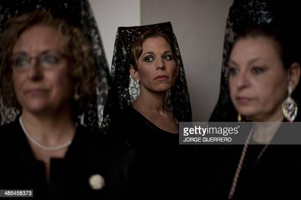 Women wearing a traditional 'Mantilla' wait to take part in the procession of 'the Clemency' brotherhood during the Holy Week in Malaga on April 17...