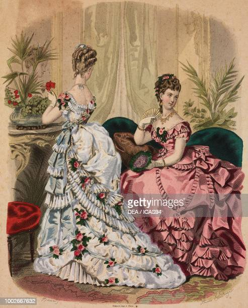Women wearing a white evening dress with flowers and pink evening dress Madame Fladry designs France coloured engraving from La Mode Illustree No 48...