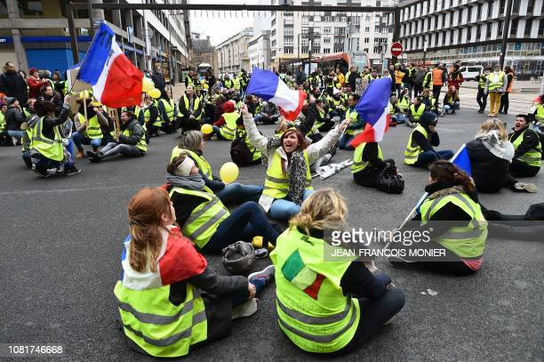 Women wearing a yellow vest wave French flags and sit in the street, on the way to the new police station in Le Mans, on January 13 to protest...