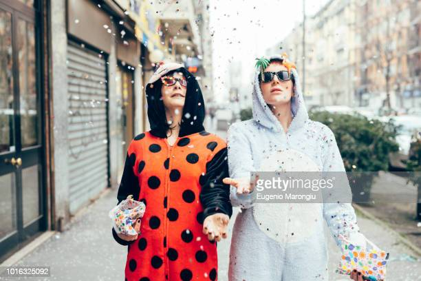 women wearing adult bodysuits throwing confetti in street - bodysuit stock pictures, royalty-free photos & images