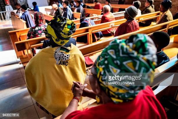 Women wearing African National Congress regalia pray during the Sunday service at the iconic Regina Mundi Church in Soweto Johannesburg on April 08...