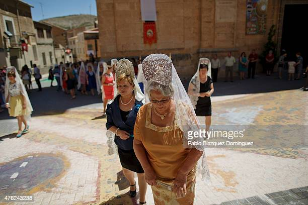 Women wearing back comb take part in a procession as they walk over a sawdust carpet during the Corpus Christi feast on June 7 2015 in Elche de la...