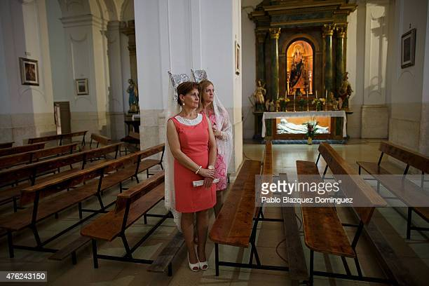 Women wearing back comb wait for the return of a procession after going through the sawdust carpets during the Corpus Christi feast on June 7 2015 in...