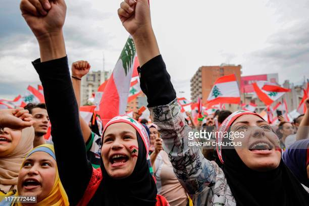 TOPSHOT Women wearing bandanas showing the Lebanese national flag chant slogans during a demonstration in the northern city of Tripoli's alNour...