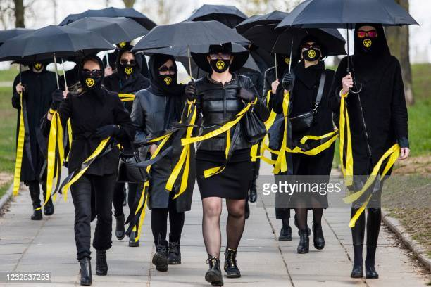 Women wearing black clothing and face masks with radioactivity sign march under umbrellas in Minsk, on April 26 to commemorate the victims of the...