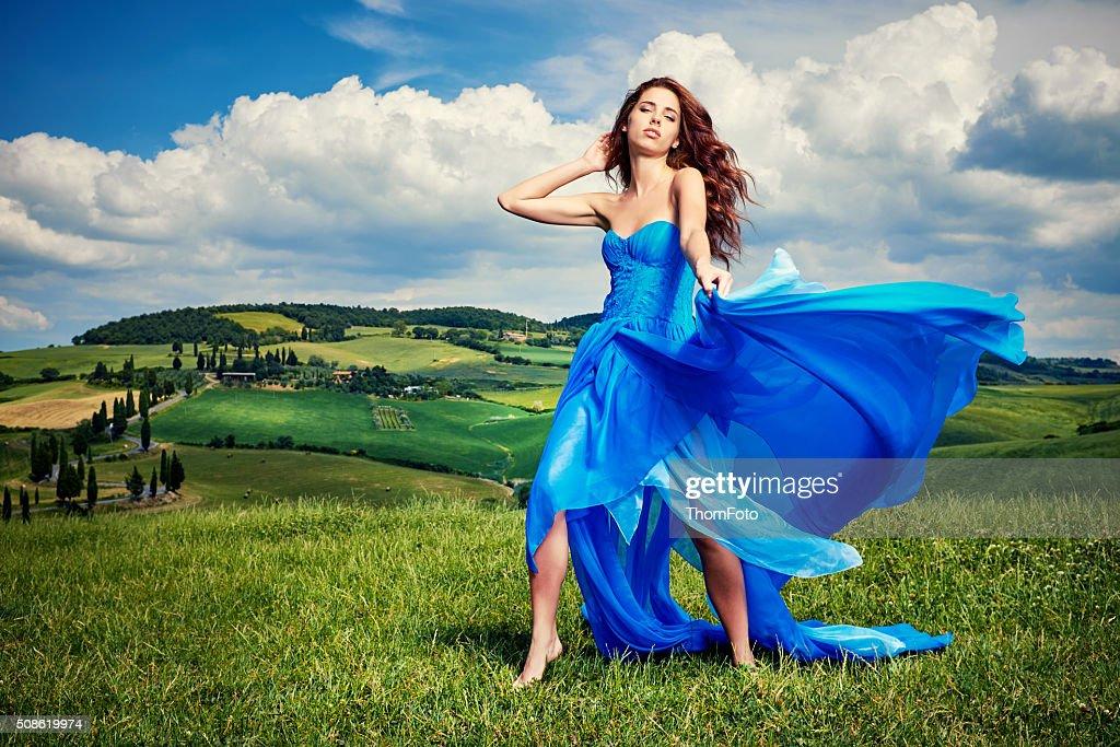 Women wearing blue long dress at sunset in Tuscany field. : Stock Photo