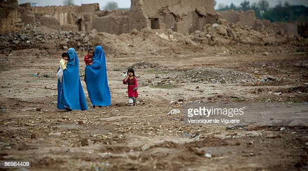 Women wearing burqas walk through a former refugee camp pictured on March 26 2009 in Peshawar NorthWest Frontier Province Pakistan