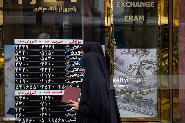 Women wearing chadors pass the window of a currency exchange store on Ferdowsi street in Tehran Iran on Saturday Jan 6 2018 A wave of bad loans from...