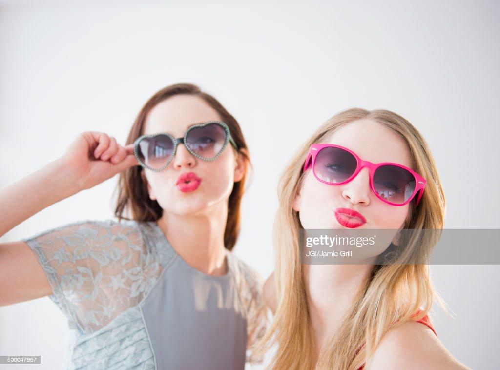 Women wearing colorful sunglasses and lipstick