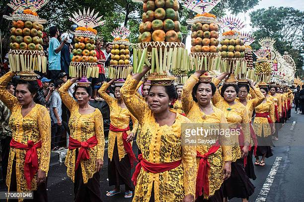 Women wearing costumes carry fruit offerings on their heads during a parade for the opening of the Bali International Arts Festival on June 15 2013...