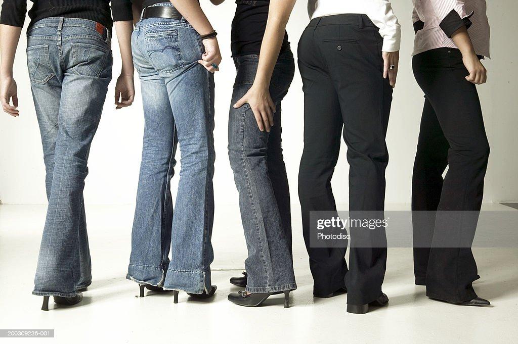 Women wearing denim jeans, posing in studio, low section : Stock Photo