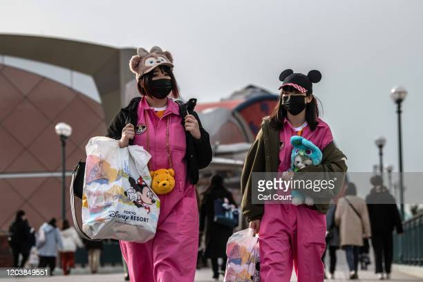 Women wearing face masks and novelty hats leave Tokyo Disneyland on the day it announced it will close until March 15th because of concerns over the...