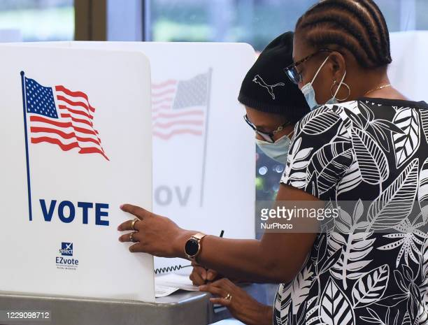 Women wearing face masks fill out votebymail ballots at the Orange County Supervisor of Elections office on October 15 2020 in Orlando Florida...