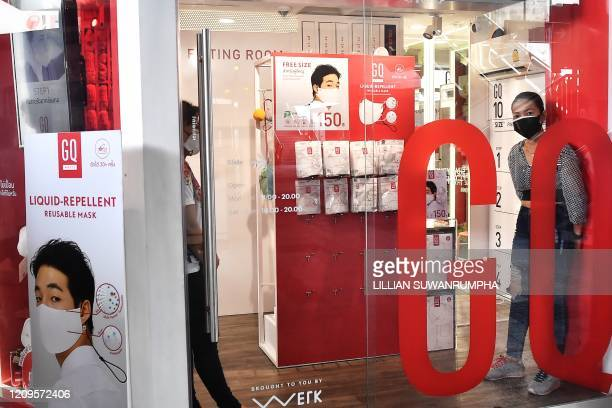 Women wearing face masks look on from a GQ store a Thai mens fashion label that has started to sell branded face masks in Bangkok on April 10 2020