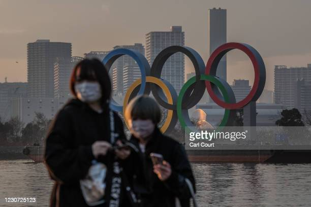 Women wearing face masks pass near the Olympic Rings on January 22, 2021 in Tokyo, Japan. With just six months to go until the start of the Games, it...