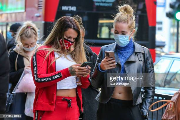 Women wearing face masks seen looking at their mobile phones in London.