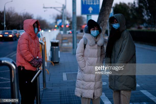Women wearing face masks stand at a bus station on a cold winter day in Beijing on December 29, 2020.