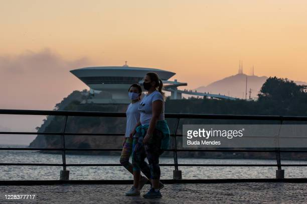 Women wearing face masks walk along a promenade with the Museum of Contemporary Art and the statue of Christ the Redeemer at the background on...