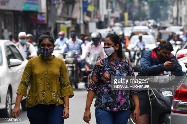 Women wearing facemask as a preventive measure against the Covid-19 Coronavirus walk along a street in Pune on September 7, 2020. - India overtook...