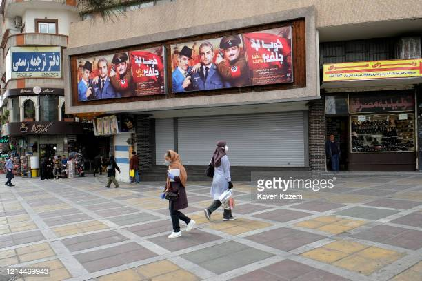 Women wearing facial masks walk outside a closed cinema in Vali Asr square on March 17 2020 in Tehran Iran