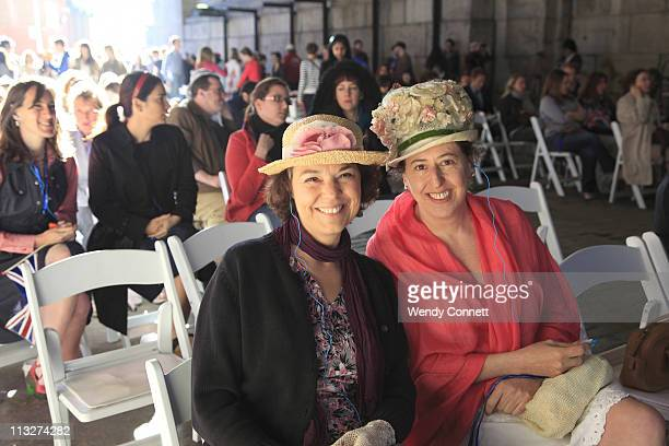 Women wearing fancy hats watch live coverage of the royal wedding projected on a giant screen under the archway of the Manhattan Bridge during the...
