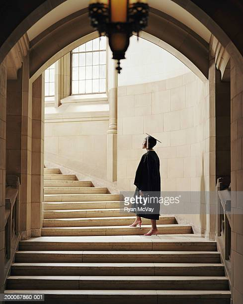 Women wearing graduation cap and gown, ascending staircase, rear view
