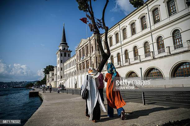 Women wearing hijab walk past the Kuleli military high school on August 4 on the shores of the Bosphorus strait in Istanbul With its twin pointed...