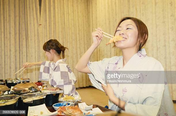 Women wearing kimonos, eating food