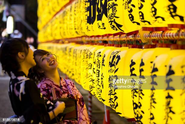 Women wearing kimonos look at lit paper lanterns during the Mitama Matsuri summer festival at Yasukuni Shrine on July 13 2017 in Tokyo Japan The...