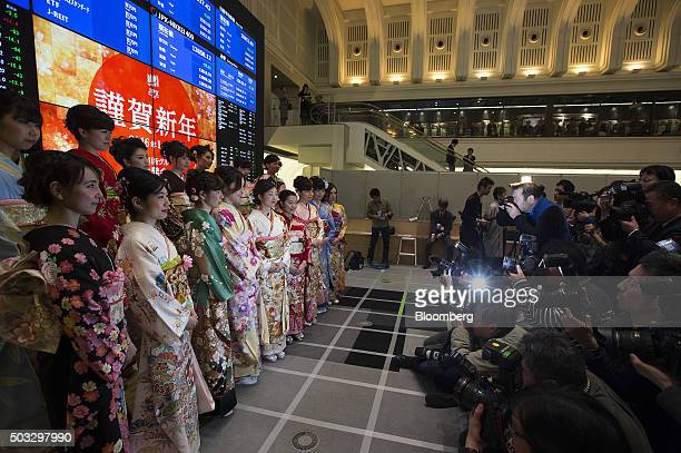 Women wearing kimonos pose for photographs during a ceremony marking the first trading day of the year at the Tokyo Stock Exchange operated by Japan...