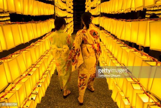 Women wearing kimonos walk through lit paper lanterns during the Mitama Matsuri summer festival at Yasukuni Shrine on July 13 2017 in Tokyo Japan The...