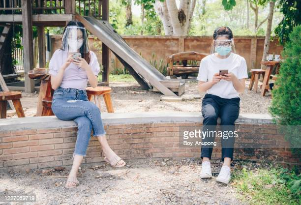 women wearing mask and face shield while sitting outdoor, keep space for avoid spreading of virus disease in covid-19 pandemic. - évitement photos et images de collection