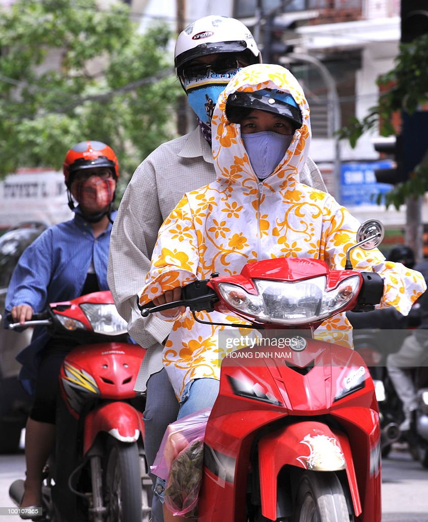 Women wearing masks and anti-sunshine shirts ride motorcycles in downtown Hanoi on May 21, 2010. The country is facing a heat wave with temperatures having reached 38-39 degree Celcius at midday in some localities. AFP PHOTO/HOANG DINH Nam