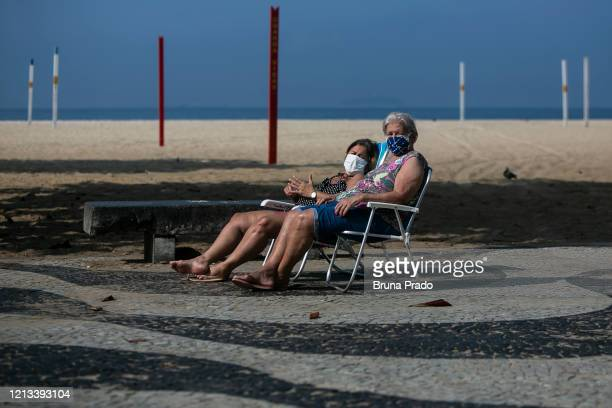 Women wearing masks sunbathe by Copacabana beach amidst the coronavirus pandemic on May 17 2020 in Rio de Janeiro Brazil The use of face masks are...