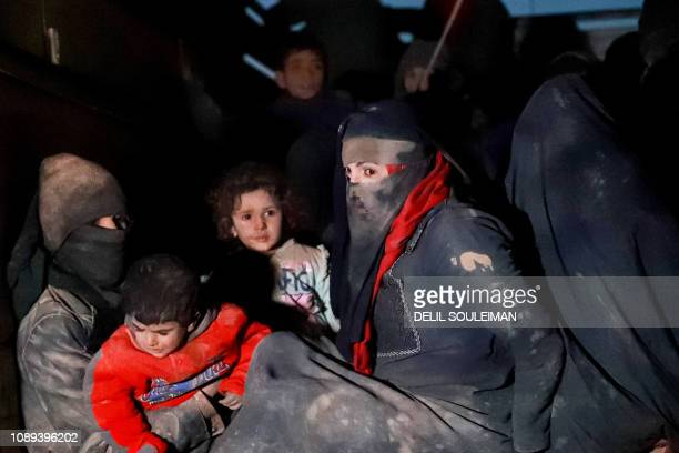 Women wearing niqabs and children with luggage are seen at the back of a truck near the Omar oil field in the countryside of the eastern Syrian Deir...