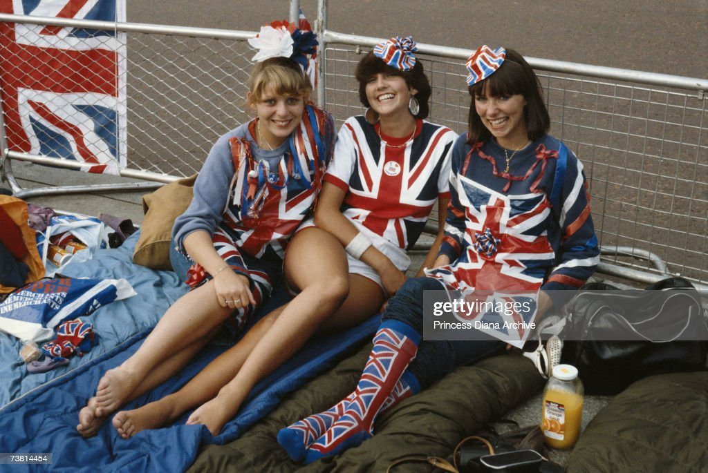 Women wearing patriotic costumes wait in London for the royal newlyweds Charles and Diana, 29th July 1981.