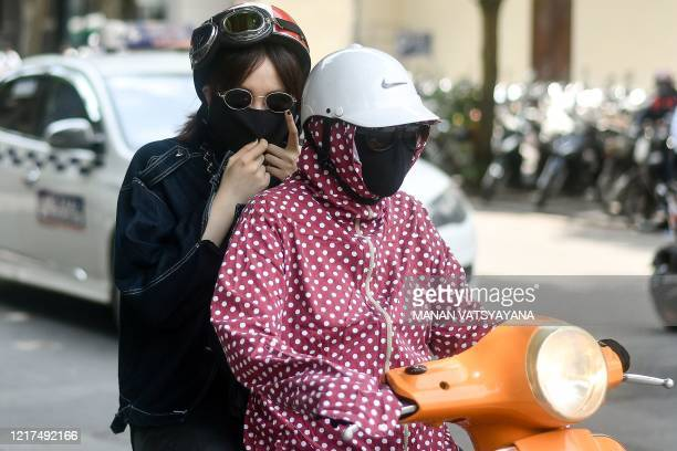 Women, wearing protective clothing to shield from the sun, ride on a scooter as the temperature soars in Hanoi on June 4, 2020.