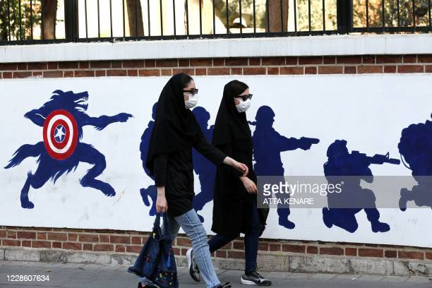 Women, wearing protective masks amid the COVID-19 pandemic, walk past a mural painted on the outer walls of the former US embassy in the Iranian...